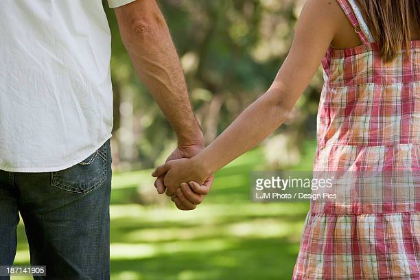 Father And Daughter Holding Hands Walking In The Park