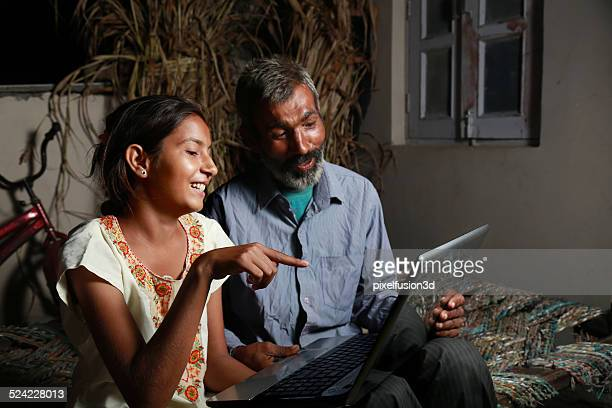 Father and Daughter Holding Laptop