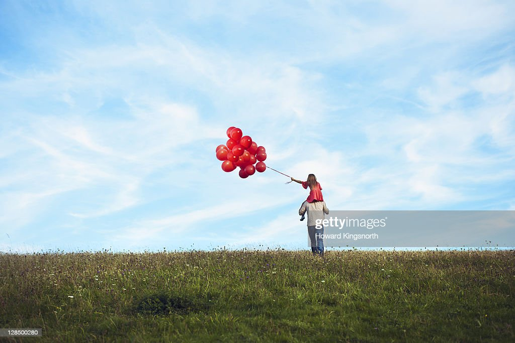 father and daughter holding red balloons : Stock Photo