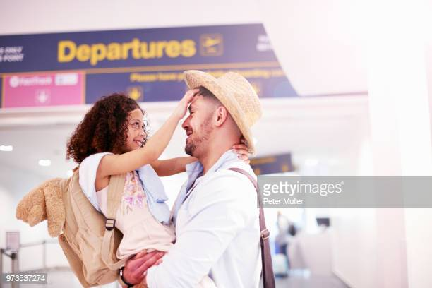 father and daughter hugging at departure lounge of airport - kid in airport stock-fotos und bilder
