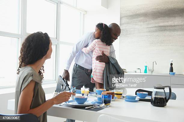 Father and daughter hugging in kitchen