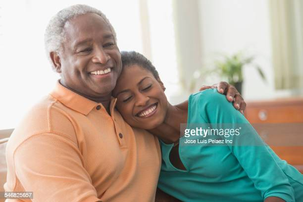 Father and daughter hugging on sofa in living room