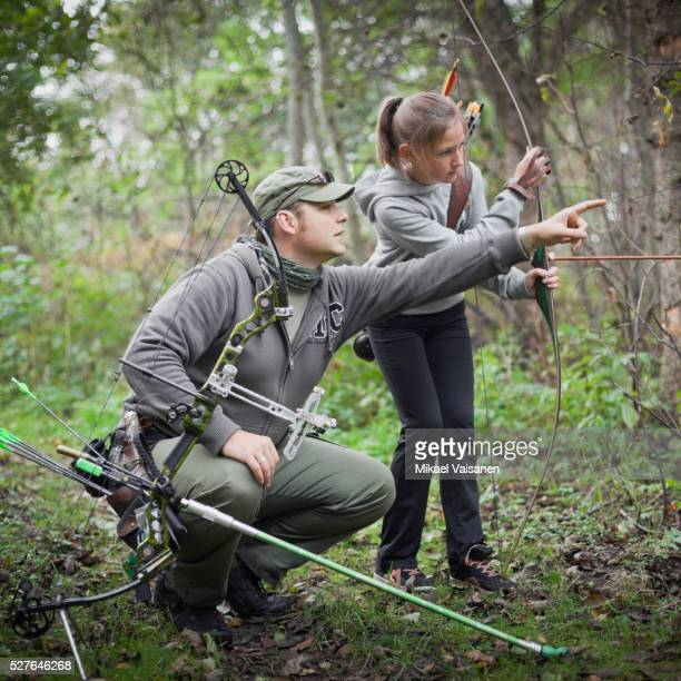 Father and daughter (10-12) hunting with bow and arrow