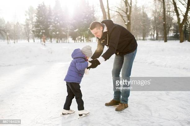 father and daughter ice skating on frozen lake - wintersport stock pictures, royalty-free photos & images