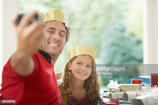 Father and daughter in Christmas crowns taking self-portrait