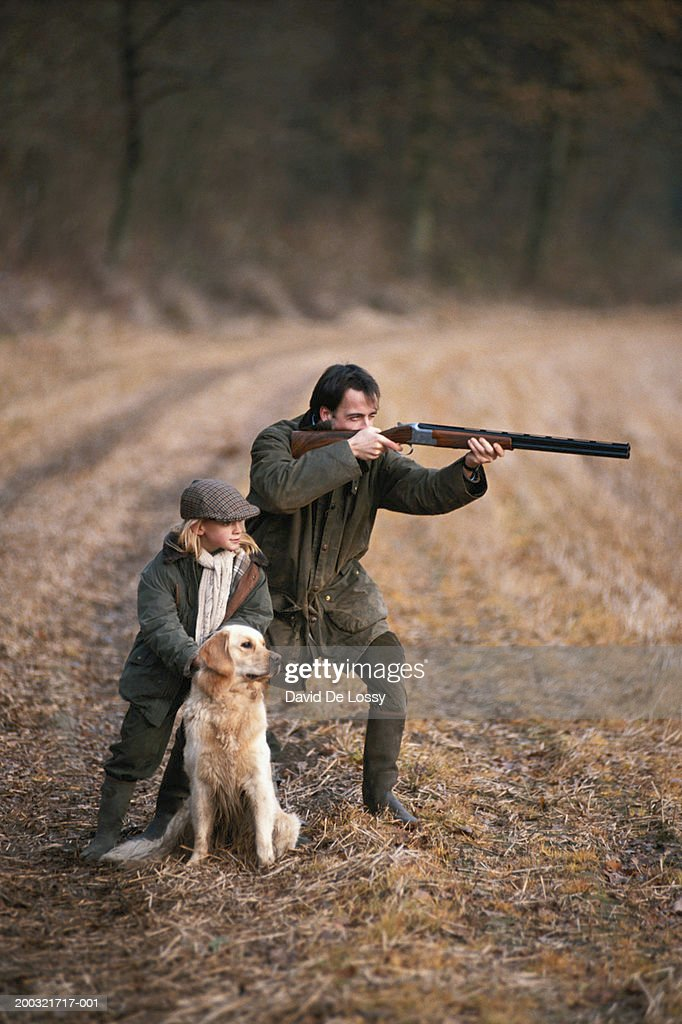 Father and daughter (4-7) in forest, man aiming with shotgun : Stock Photo