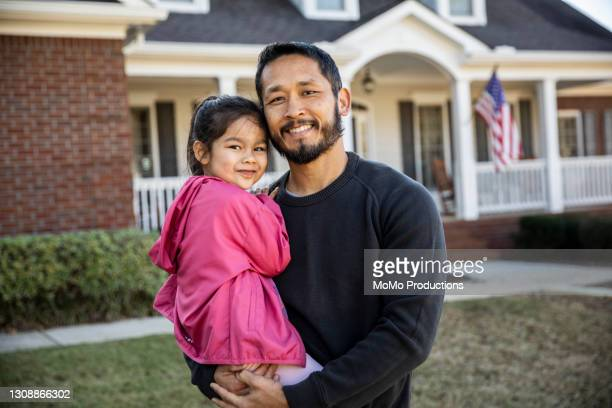 father and daughter in front of suburban home - mortgage stock pictures, royalty-free photos & images