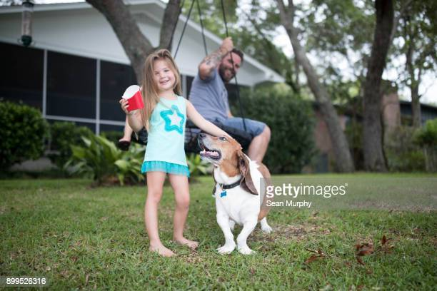 Father and daughter in garden with pet dog