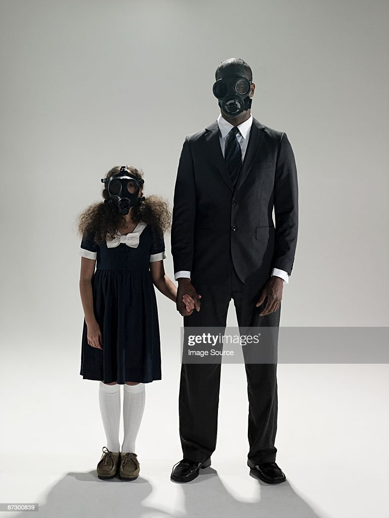 Father and daughter in gas masks : Stock Photo
