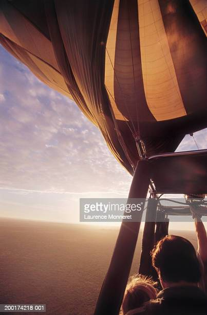 Father and daughter (6-8) in hot air balloon, sunrise