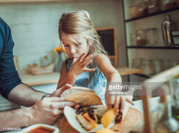 father and daughter in kitchen at home making tortillas - tortilla flatbread stock pictures, royalty-free photos & images