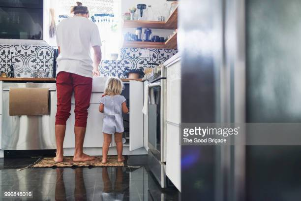 father and daughter in kitchen at home - routine stock-fotos und bilder