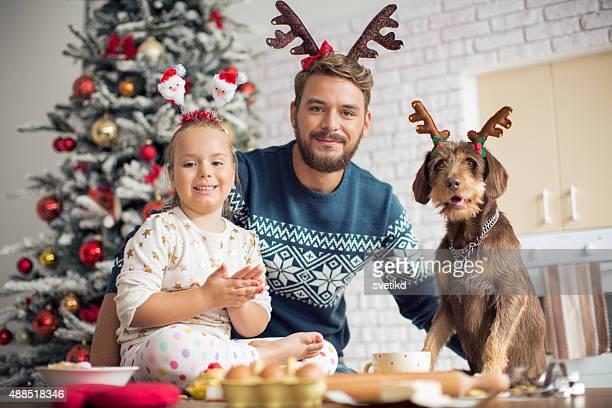 Padre e figlia in cucina per Natale con il loro cane.