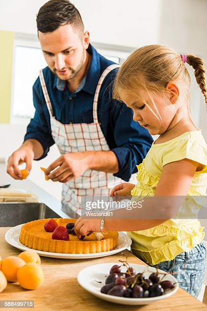 father and daughter in kitchen preparing fruit cake - putting stock pictures, royalty-free photos & images
