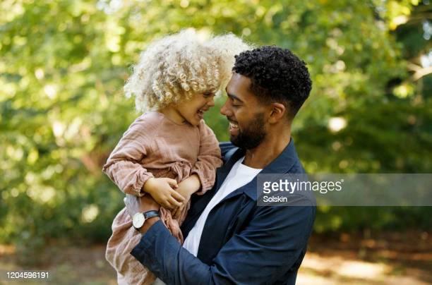 father and daughter in park, having fun together - gemengde afkomst stockfoto's en -beelden