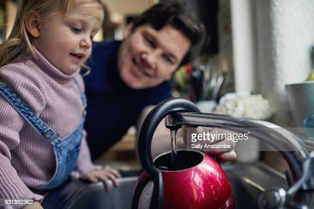 father and daughter in the kitchen together holding a kettle - red kettle stock photos and pictures