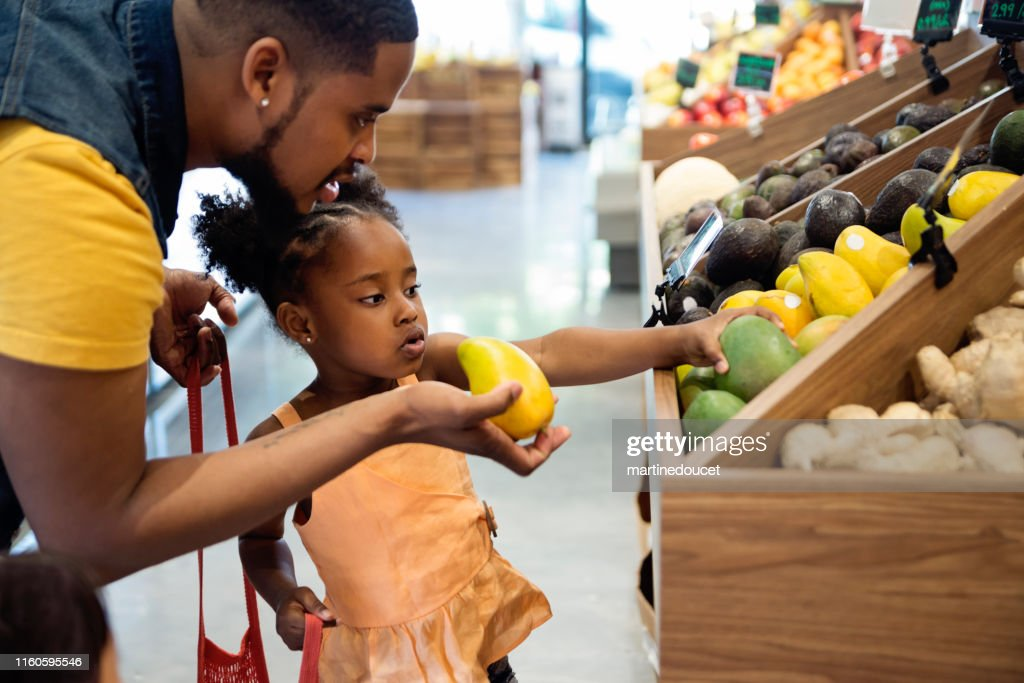 Father and daughter in zero waste oriented fruit and grocery store. : Stock Photo