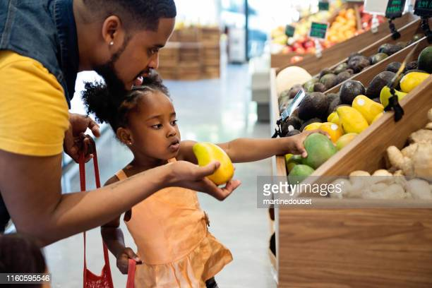 "father and daughter in zero waste oriented fruit and grocery store. - ""martine doucet"" or martinedoucet stock pictures, royalty-free photos & images"