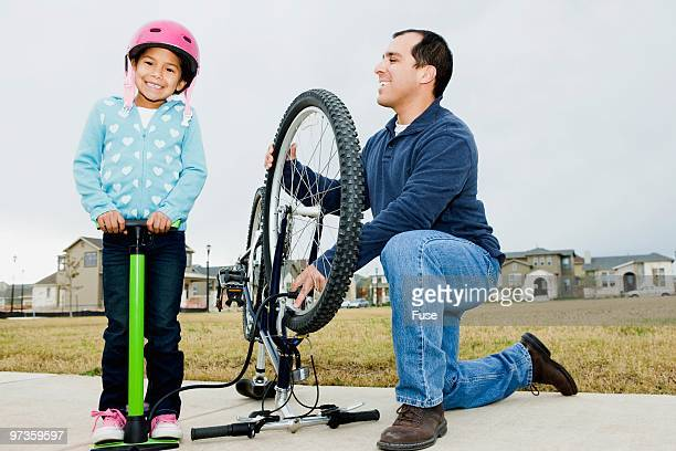 father and daughter inflating bicycle tire - air pump stock photos and pictures