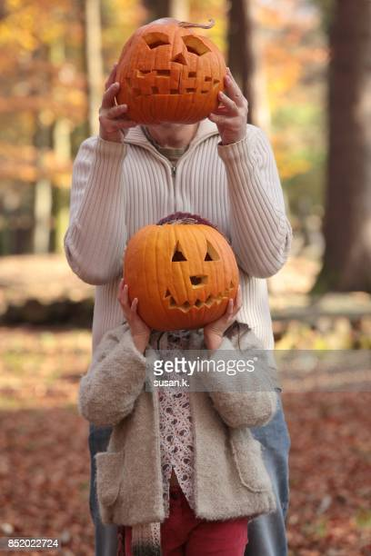 father and daughter jack o' lantern - scary pumpkin faces stock photos and pictures