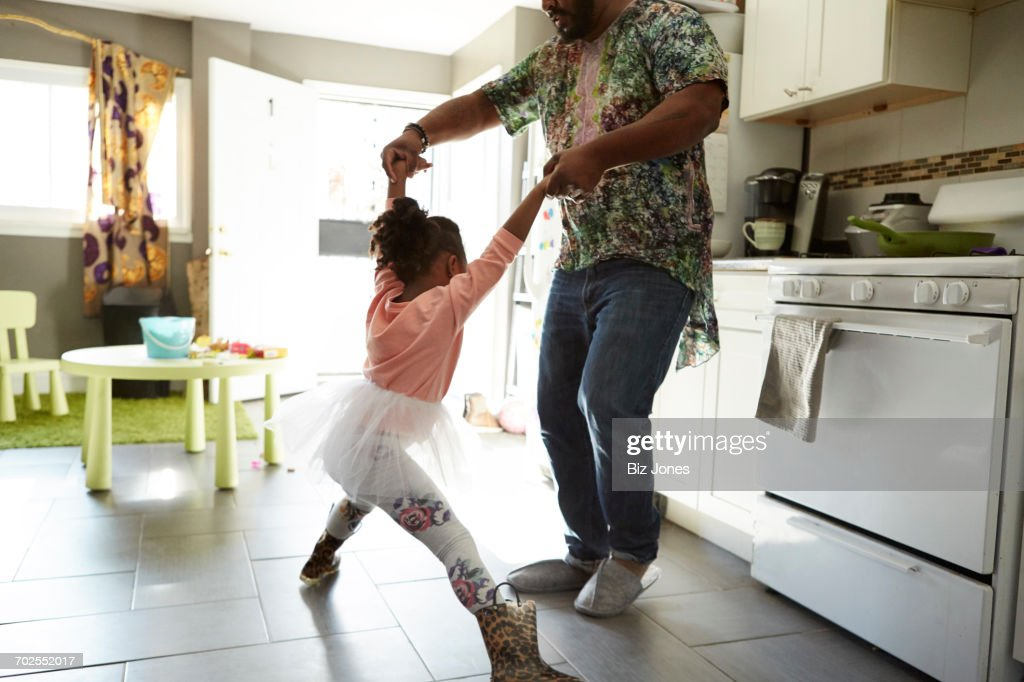 Father and daughter jiving in kitchen : Stock Photo