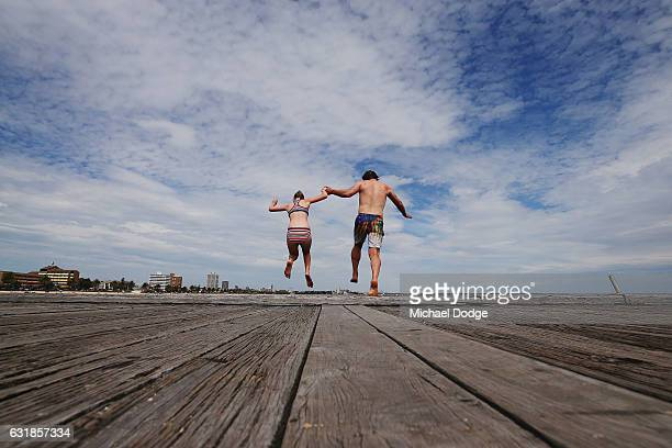 Father and daughter jump off the pier at South Melbourne Beach on January 17 2017 in Melbourne Australia Temperatures reached above 30 degrees...