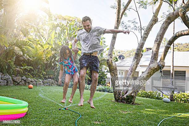 Father and daughter jumping in sprinkler at backyard garden