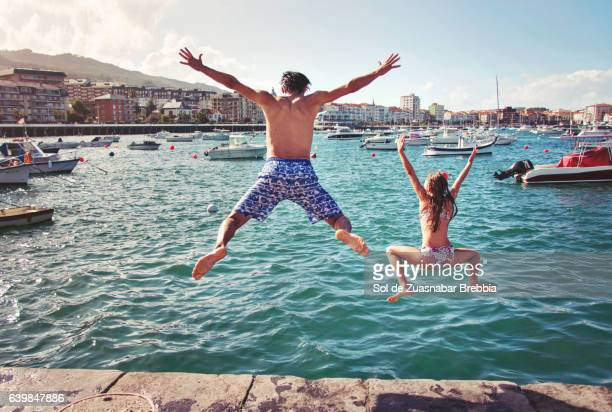 Father and daughter jumping into sea in a beautiful harbor