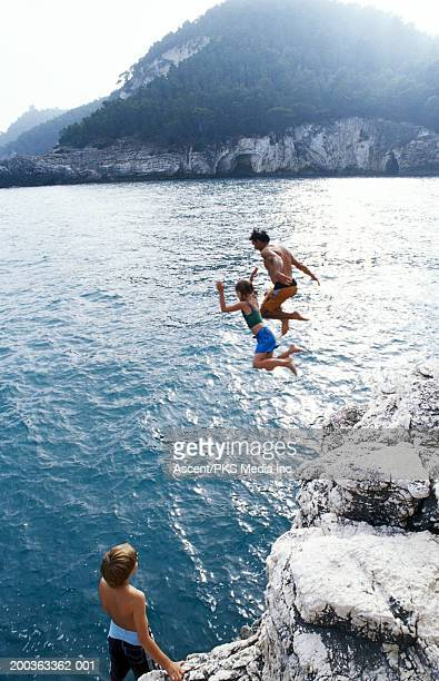 Father and daughter jumping off cliff