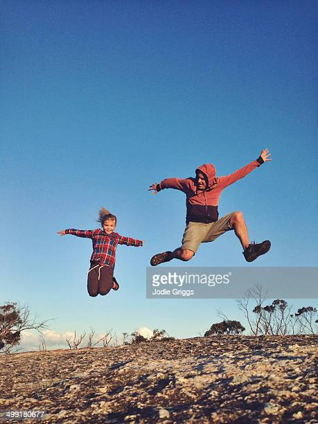 Father and daughter jumping off rock into the air