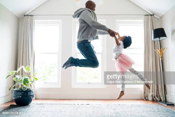 father and daughter jumping while doing ballet - african american family home stock photos and pictures