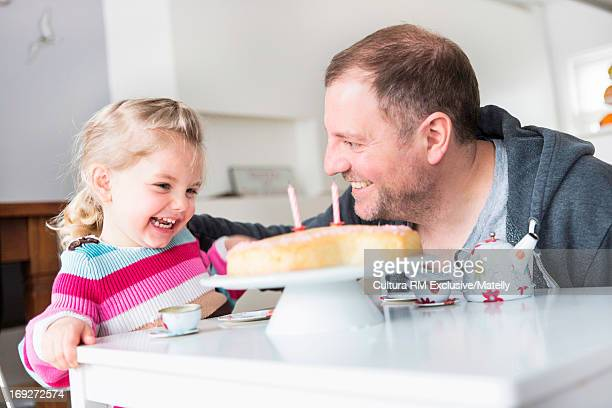 Father and daughter laughing at tea party with cake