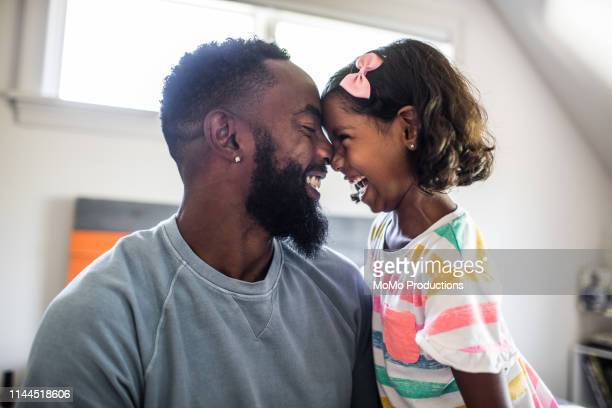father and daughter laughing in bedroom - black photos et images de collection