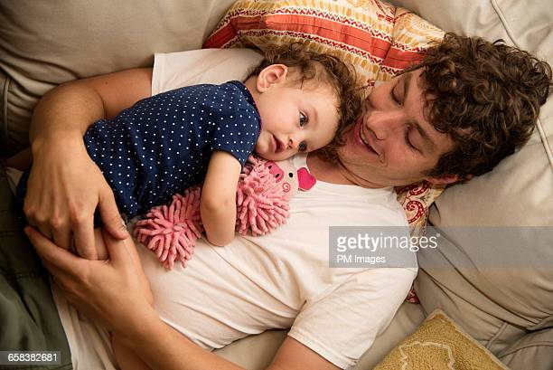 Father and daughter laying on couch