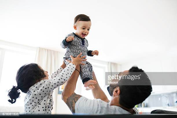 Father and daughter lifting toddler at home