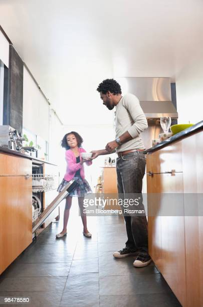 Father and daughter loading dishwasher