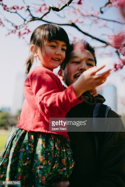 Father and daughter looking at Japanese plum blossoms, Tokyo