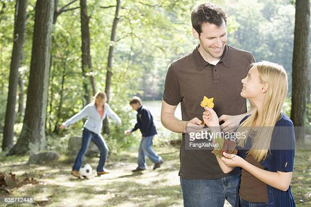 father and daughter looking at leaves together in nature - the god father stock photos and pictures