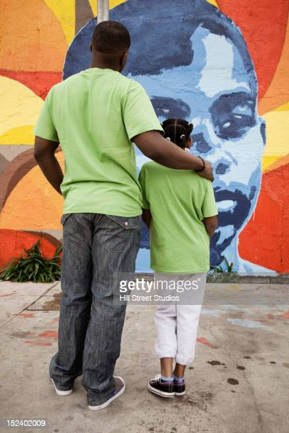 Father and daughter looking at mural