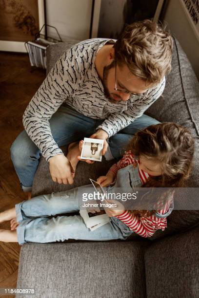 father and daughter looking at pictures - transfer image stock pictures, royalty-free photos & images
