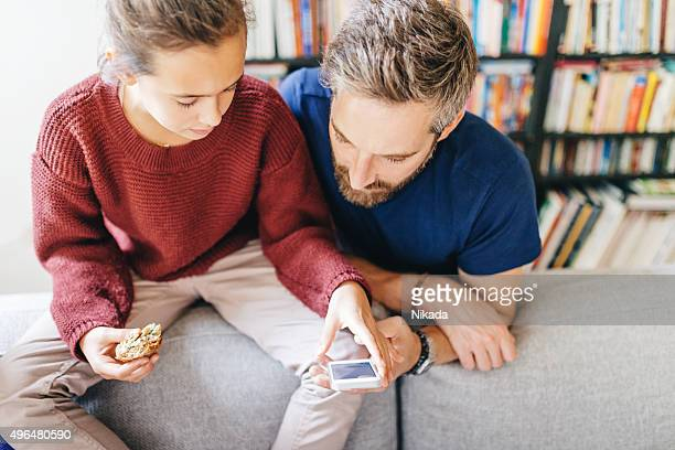 father and daughter looking at smartphone