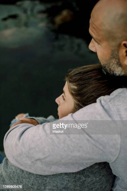 father and daughter looking away while sitting by lake - affectionate stock pictures, royalty-free photos & images