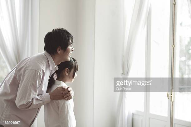 father and daughter looking out,smiling