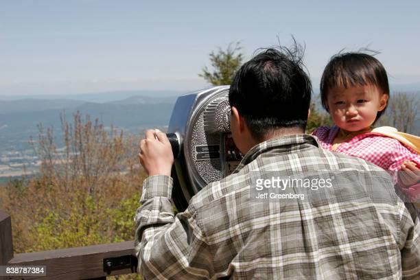 Father and daughter looking through a telescopic viewer at Skyland Resort.