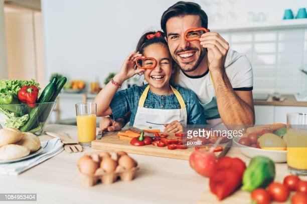 Father and daughter looking through pepper slices