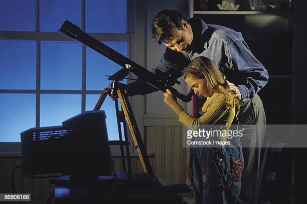 Father and daughter looking through telescope