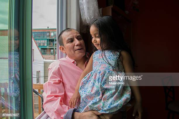 Father and daughter looking trough the window