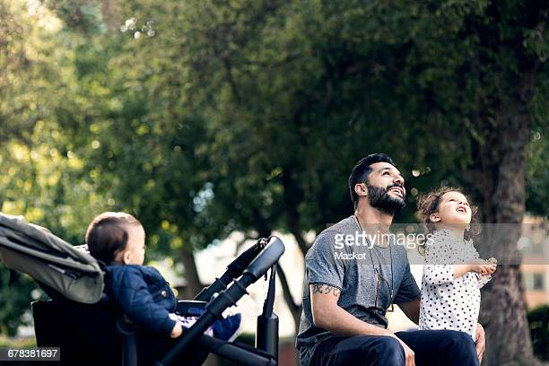 Father and daughter looking up while sitting on bench by baby stroller at park