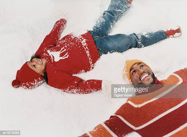 Father and Daughter Lying in Snow