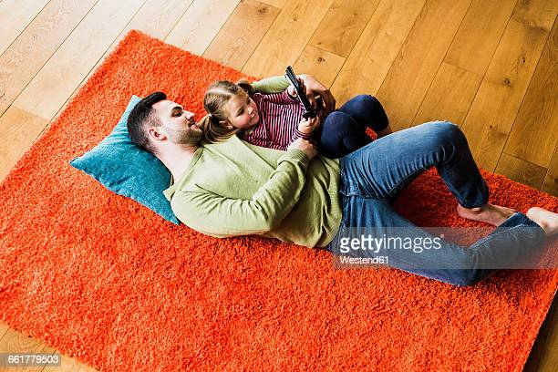 Father and daughter lying on carpet on the floor using digital tablet